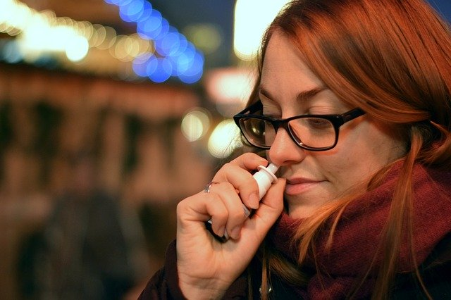 žena si stříká kapky do nosu