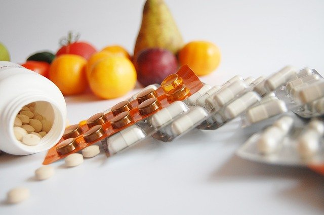 plata s léky, bílé kapsle, v pozadí ovoce